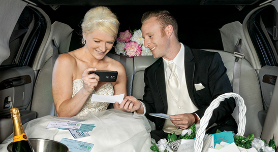 Bride and groom taking a photo of a check with a cell phone.