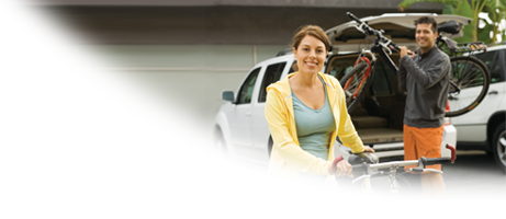 Woman on bicycle, man taking bicycle from car.