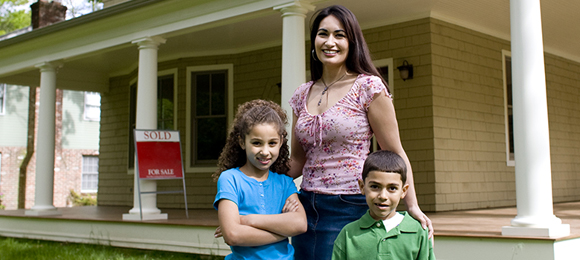 "Woman with two children standing in front of house with ""Sold"" sign leaning against porch."