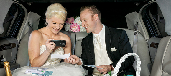 Image of newlywed couple in limousine using a mobile phone to make a mobile check deposit.
