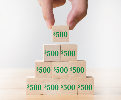 Hand stacking $500 blocks in to a pyramid.
