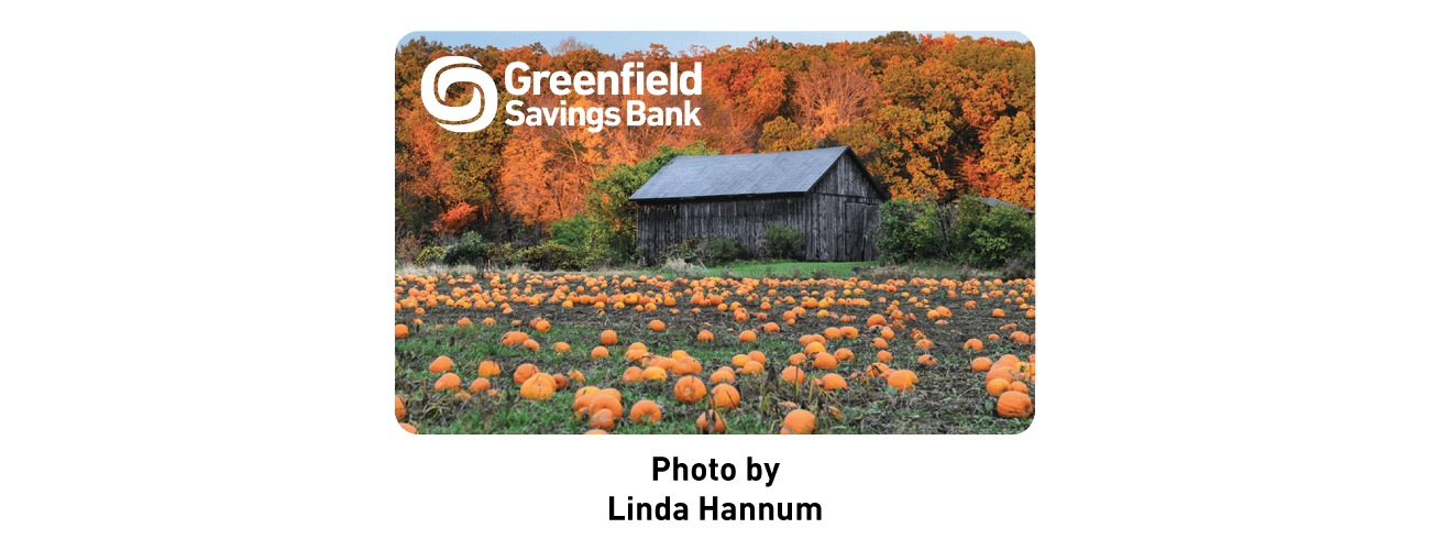 Greenfield savings bank logo on a photo of a pumpkin patch with a barn and foliage, Photo by Linda Hannum.