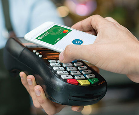 Using touch-free payments at a register with a GSB debit card linked to a phone's mobile wallet.