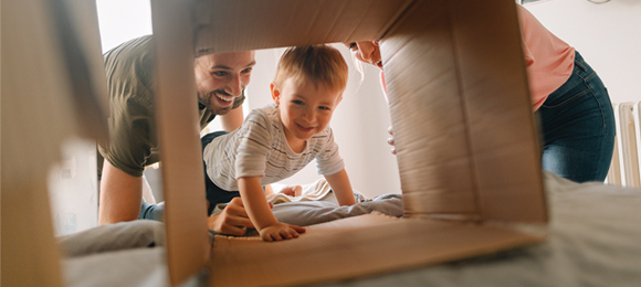 Baby crawling through open cardboard moving box, with parents watching behind him.